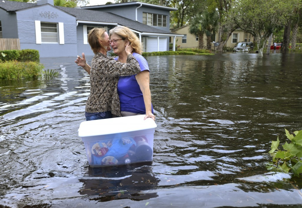 Charlotte Glaze gives Donna Lamb a teary hug as she floats out some of her belongings in floodwaters from the Ortega River in Jacksonville, Fla., Mond...