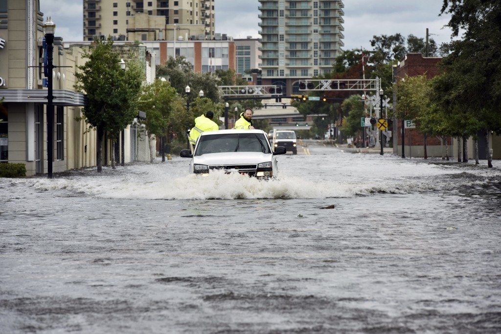 Police officers plow through floodwater on Hendricks Avenue in San Marco as Hurricane Irma passes by Monday, Sept. 11, 2017, in Jacksonville, Fla. (Wi...