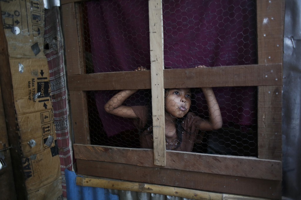 In this Sunday, Sept. 10, 2017, photo, a Rohingya girl peeps out from her temporary shelter at a camp in Kathmandu, Nepal. Recent violence in Myanmar ...
