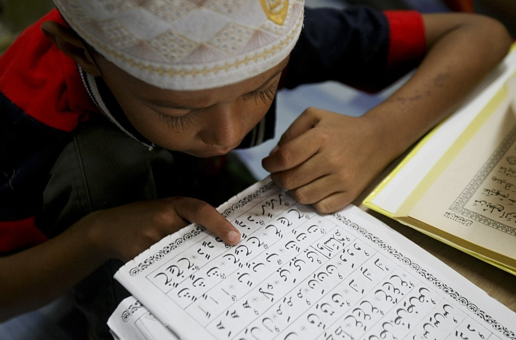 In this Tuesday, Sept. 12, 2017, photo, a Rohingya Muslim child living in Malaysia recites from the holy Quran at a school in Klang, on the outskirts ...