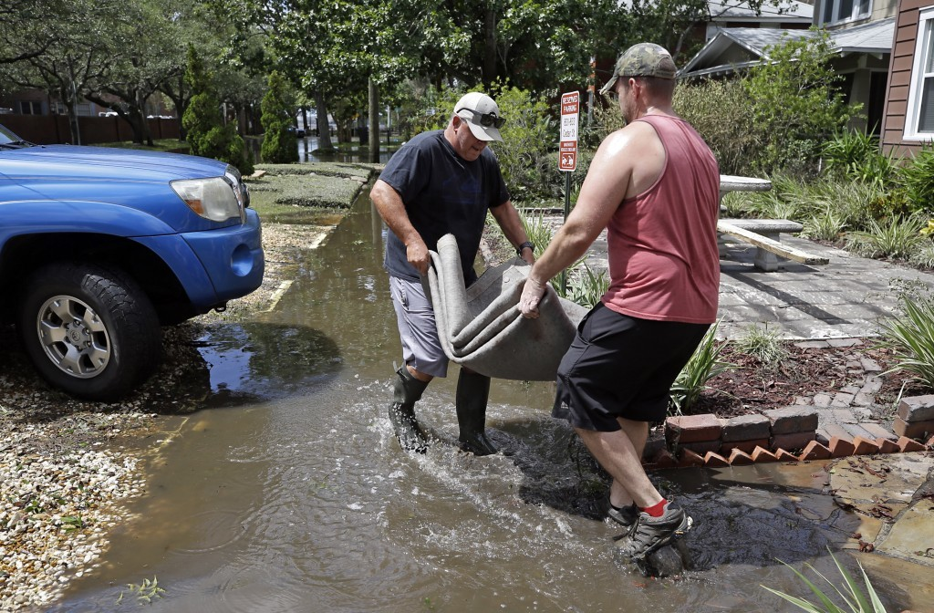 Jeff Moore, left, helps building owner Gary Boggs remove a water logged rug from a flooded two story building in the San Marco area of Jacksonville, F...