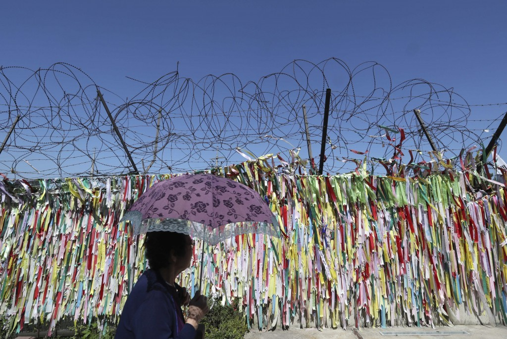 In this Wednesday, Sept. 13, 2017 file photo, a visitor walks by the wire fence decorated with ribbons carrying messages to wish for the reunification...