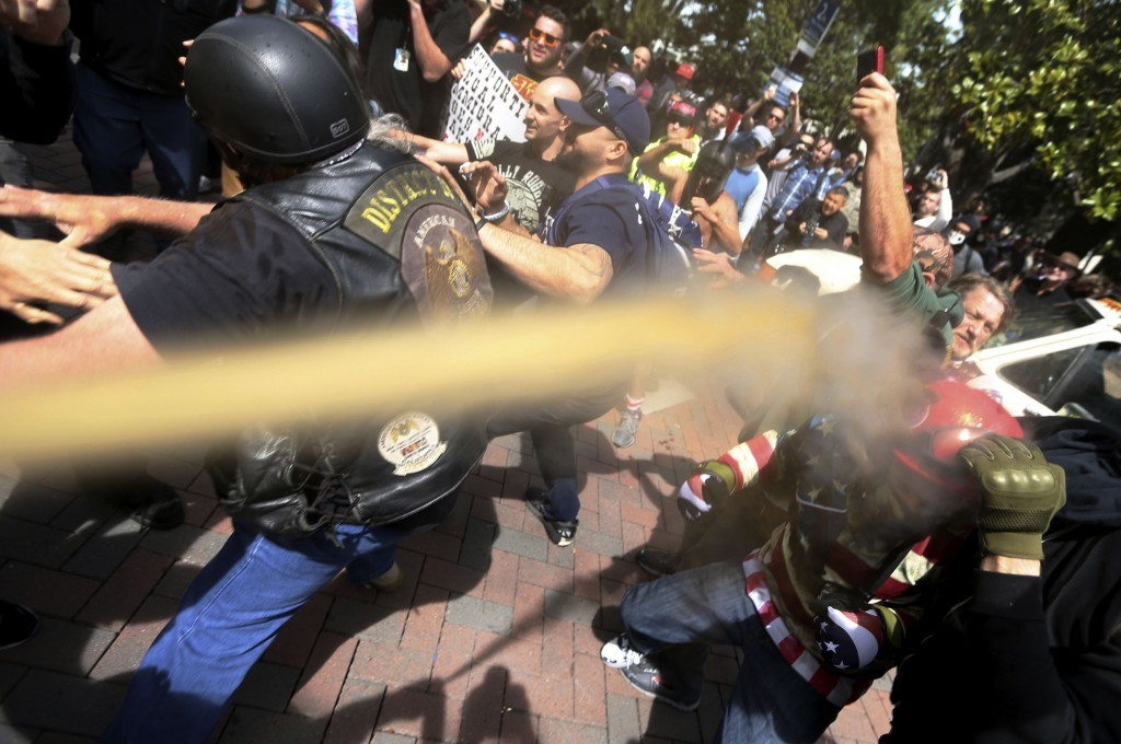 FILE - In this April 15, 2017 file photo, pepper spray is used as anti and pro-Donald Trump protesters clash during competing demonstrations at Martin...