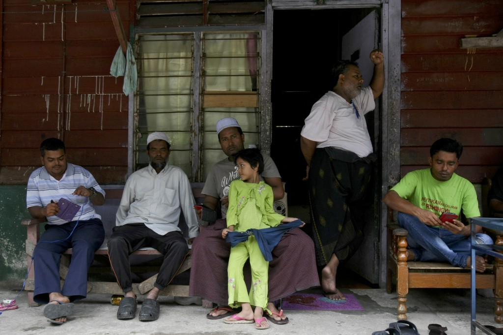 In this Tuesday, Sept. 12, 2017, photo, Rohingya Muslims living in Malaysia rest outside a house in Klang, on the outskirts of Kuala Lumpur, Malaysia....