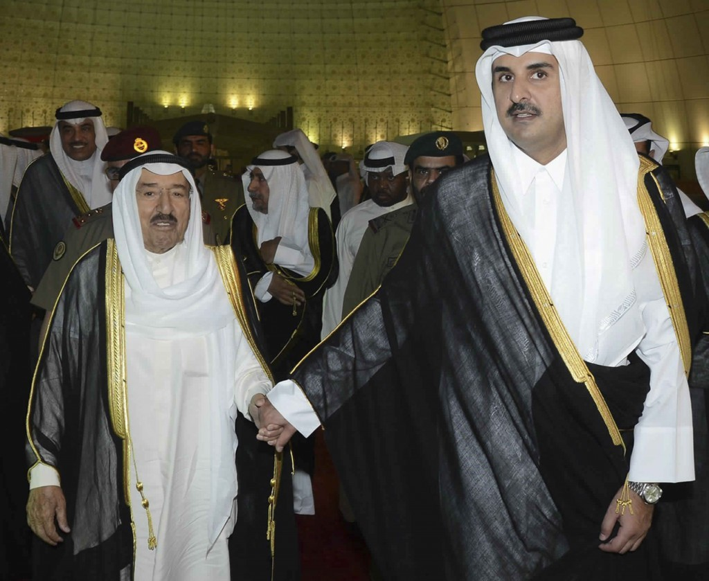 FILE- In this June 7, 2017 file photo, released by Kuwait News Agency, KUNA, Kuwait's Emir Sheikh Sabah Al Ahmad Al Sabah, left, holds the hand of Qat...