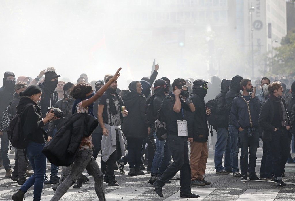 Demonstrators gesture after clashing with police during a protest march against President Emmanuel Macron's new pro-business labor policies in Paris, ...