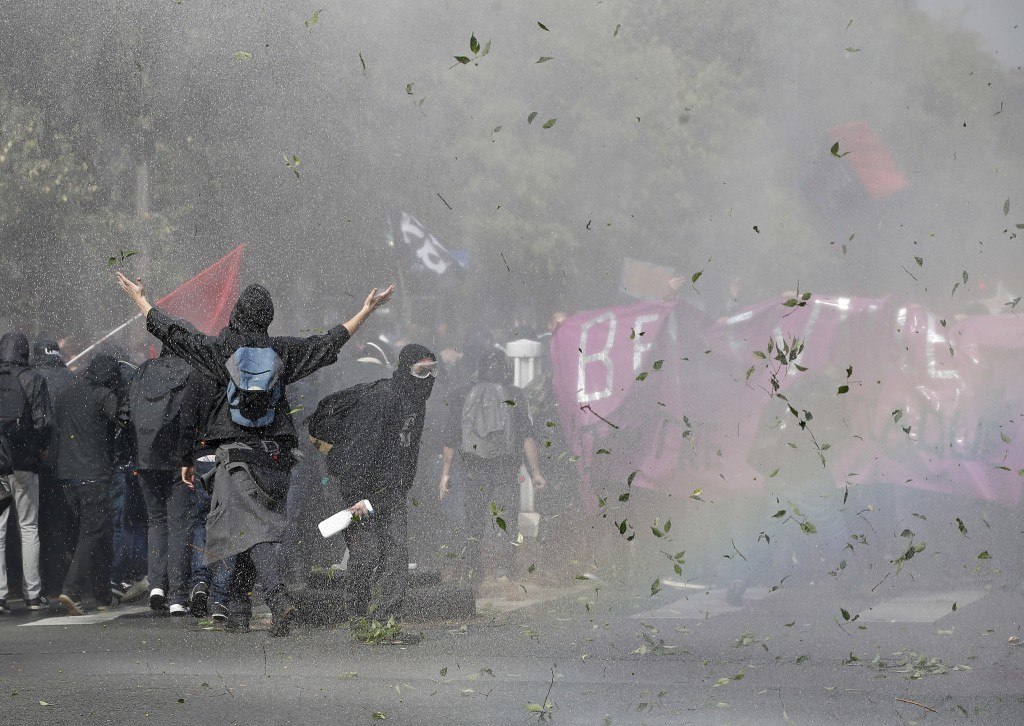 Demonstrators take cover after clashing with police during a protest march against President Emmanuel Macron's new pro-business labor policies in Pari...