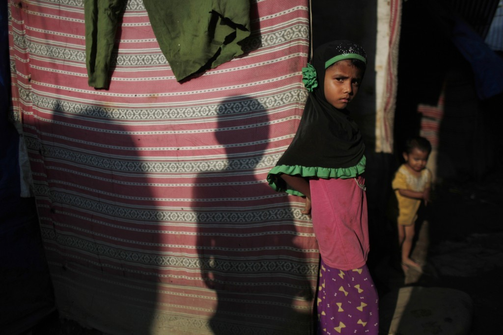 In this Sunday, Sept. 10, 2017, photo, a young Rohingya stands outside her temporary shelter at a camp in Kathmandu, Nepal. Recent violence in Myanmar...