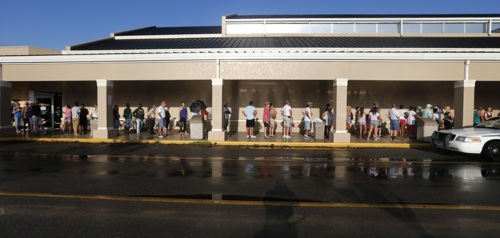 People line up for the announced opening of a Publix grocery store, the first food chain to re-open in Naples, in the aftermath of Hurricane Irma, whi...