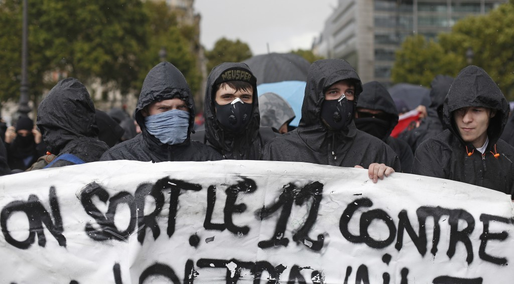 Protestors with their faces covered march against President Emmanuel Macron's new pro-business labor policies in Paris, Tuesday, Sept. 12, 2017. Macro...