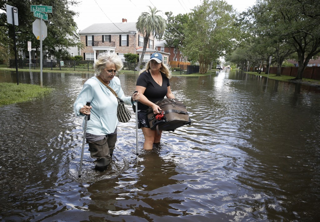 Marlene Sulkers, left, is escorted by her granddaughter Rachel Sulkers as they evacuate from Rachel's residence in the aftermath of Hurricane Irma, in...