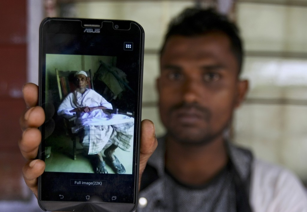 In this Tuesday, Sept. 12, 2017, photo, Rohingya refugee Muhammad Ayub shows off a picture of his grandfather allegedly killed during recent violence ...