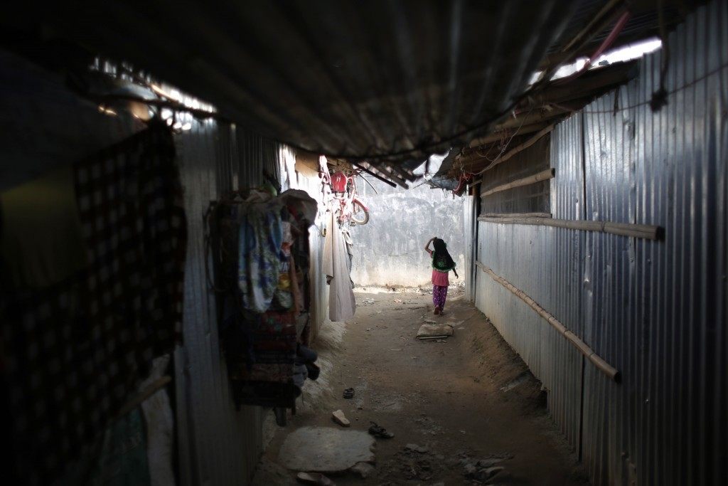 In this Sunday, Sept. 10, 2017, photo, a young Rohingya girl walks inside a temporary shelter at a camp in Kathmandu, Nepal. Recent violence in Myanma...