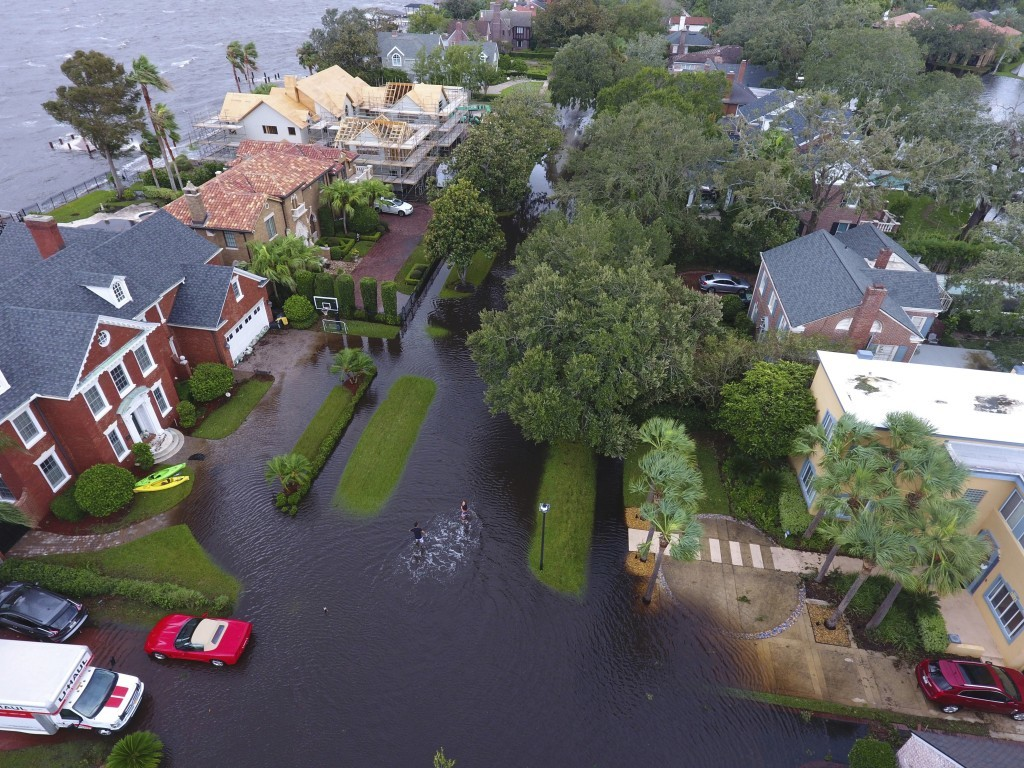 In this Monday, Sept. 11, 2017, photo provided by DroneBase, people trudge through floodwaters in the aftermath of Hurricane Irma in Jacksonville, Fla...