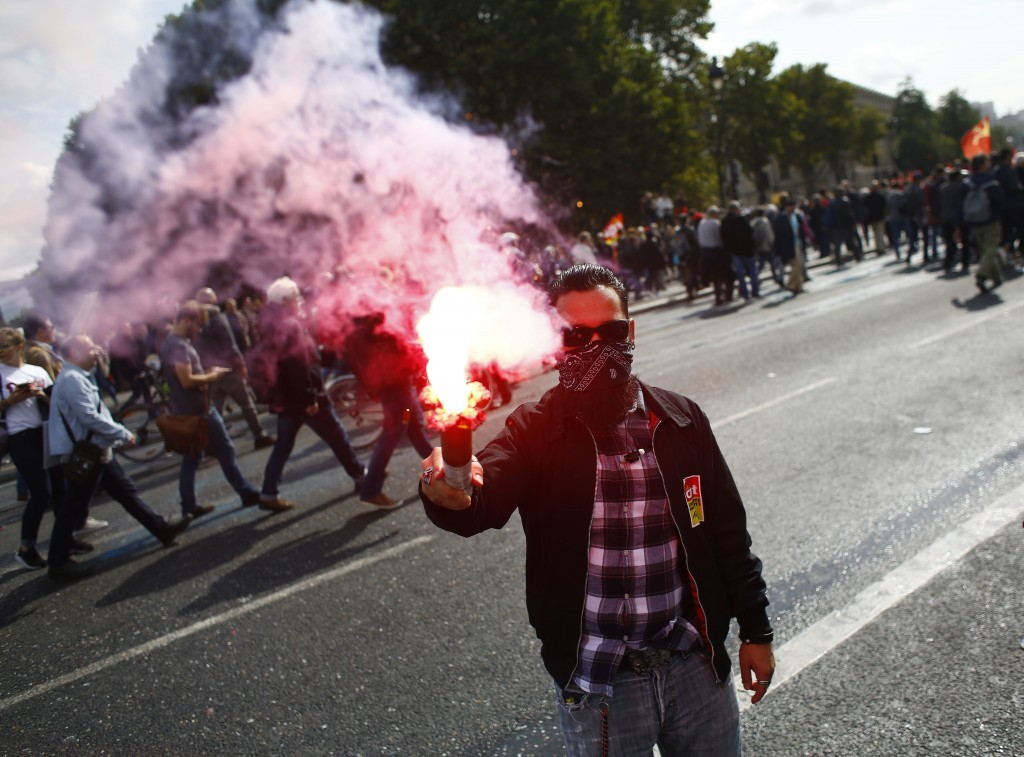 A protestor holding a flare marches against President Emmanuel Macron's new pro-business labor policies in Paris, Tuesday, Sept. 12, 2017. Macron's pr...