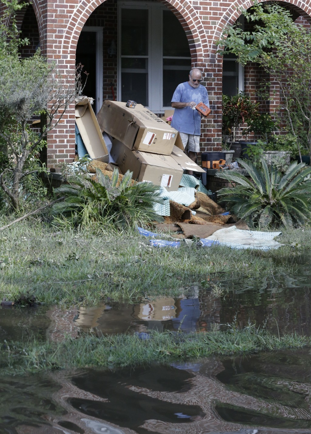 A home owner removes water logged items from his home as floodwaters fill the street in the San Marco area of Jacksonville, Fla. in the aftermath of H...