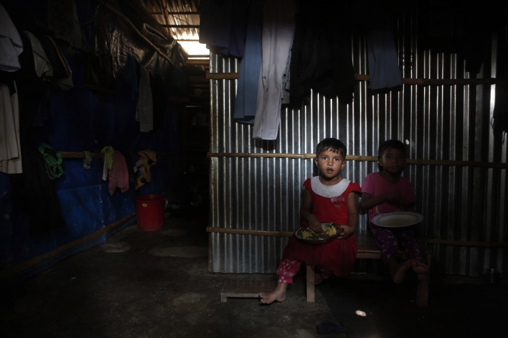 In this Sunday, Sept. 10, 2017 file photo, Rohingya children have their lunch inside a temporary shelter in a camp in Kathmandu, Nepal. Recent violenc...