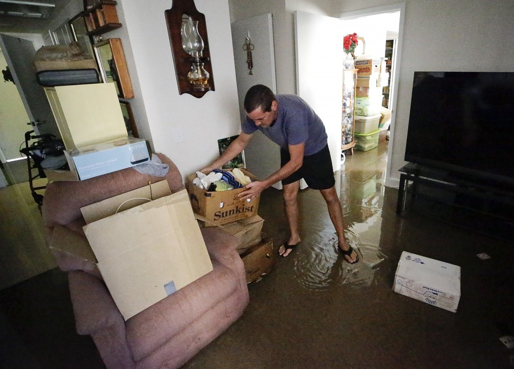 Joseph Dupuis III stacks items off the floor in his parents water logged apartment on the St. John's River in Jacksonville, Fla. in the aftermath of H...