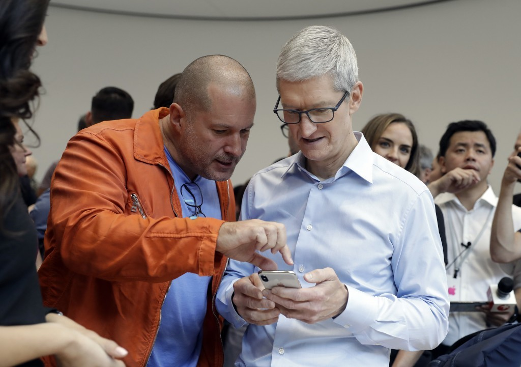 Apple CEO Tim Cook, right, and Jonathan Ive, Chief Design Officer shows the new iPhone X in the showroom after the new product announcement at the Ste...
