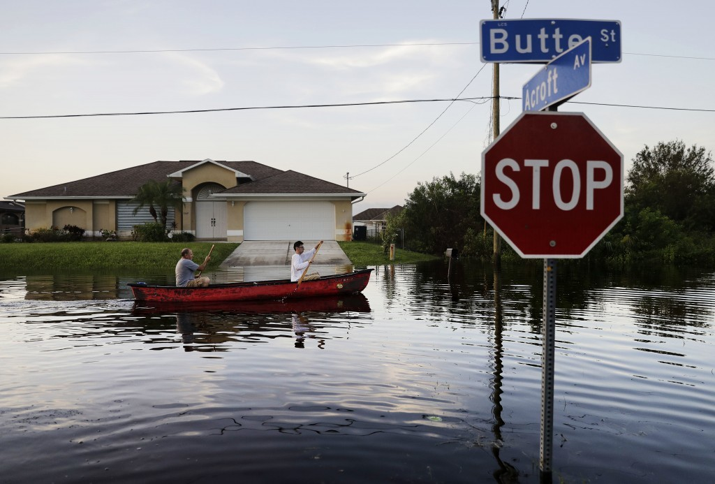 Pierre Ghantos, left, and his son Nathan paddle though their flooded neighborhood in the aftermath of Hurricane Irma in Fort Myers, Fla., Tuesday, Sep...