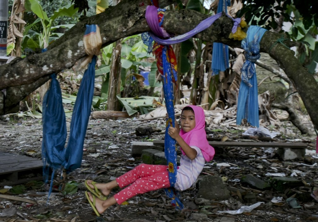 In this Tuesday, Sept. 12, 2017, photo, a Rohingya Muslim girl living in Malaysia sits on a makeshift swing outside her house in Klang, outside Kuala ...