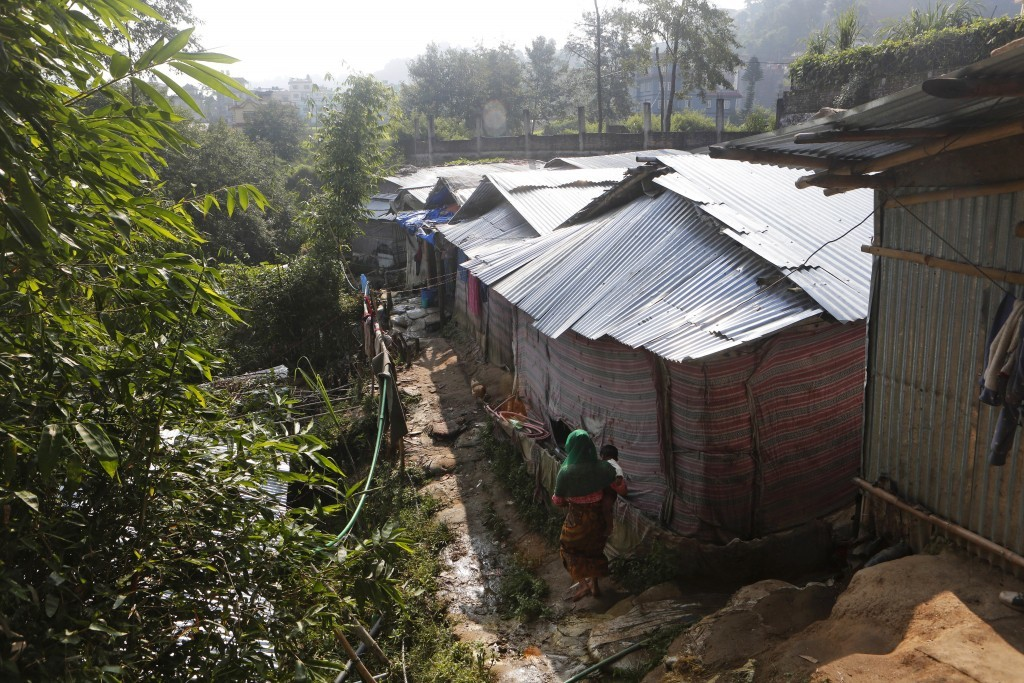 In this Sunday, Sept. 10, 2017, photo, a Rohingya woman carrying her child walks toward her temporary shelter in a camp in Kathmandu, Nepal. Recent vi...