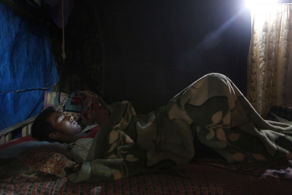 In this Sunday, Sept. 10, 2017, photo, Rohingya man checks his phone inside temporary shelter at a camp in Kathmandu, Nepal. Recent violence in Myanma...
