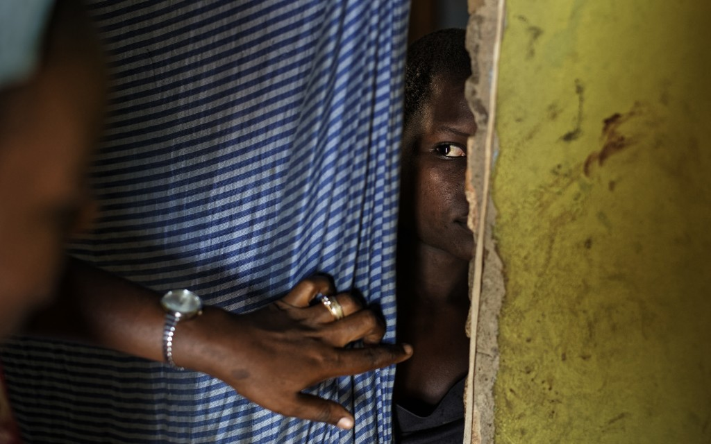 In this Thursday, June 1, 2017 photo, a 15-year-old who was raped when she was 14 talks to a member of UNICEF staff, left, at her home in a village ne...