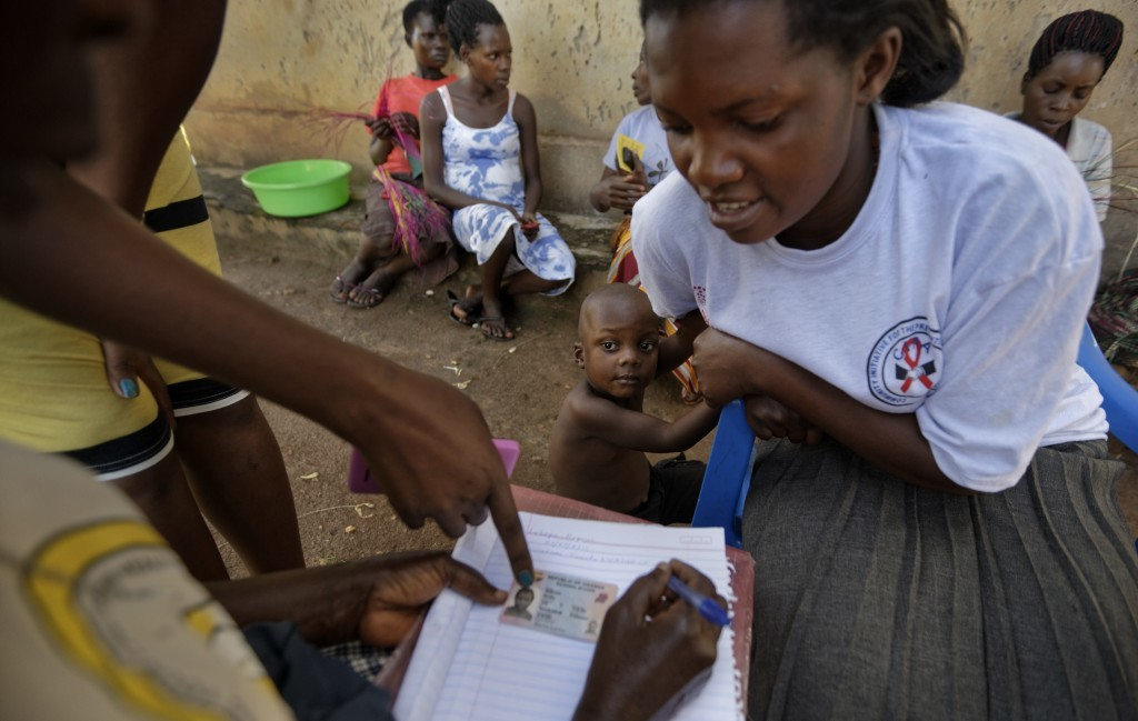 In this Thursday, June 1, 2017 photo, Felista Namotovu, 26, right, gives the details of the birth of her son, Reyman Lubega, 3, center, to health work...