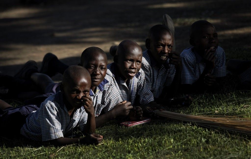 In this Wednesday, May 31, 2017 photo, children lie on the grass during break at the Side-By-Side Boetheo School, which assists mostly orphans who wer...