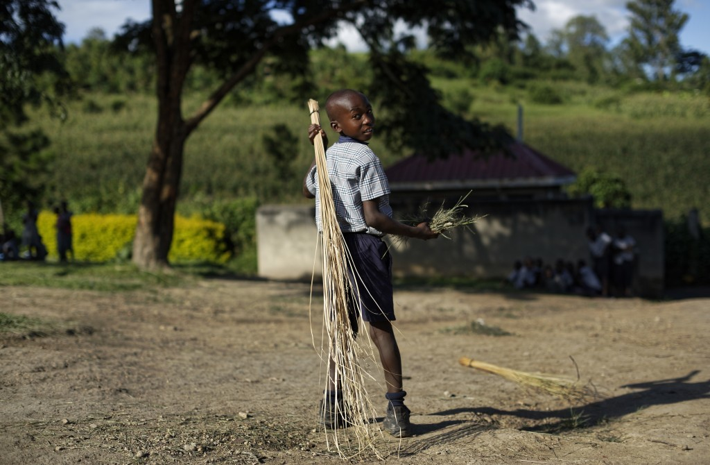 In this Wednesday, May 31, 2017 photo, a boy sweeps outside the assembly hall during break at the Side-By-Side Boetheo School in Rakai, Uganda. The sc...