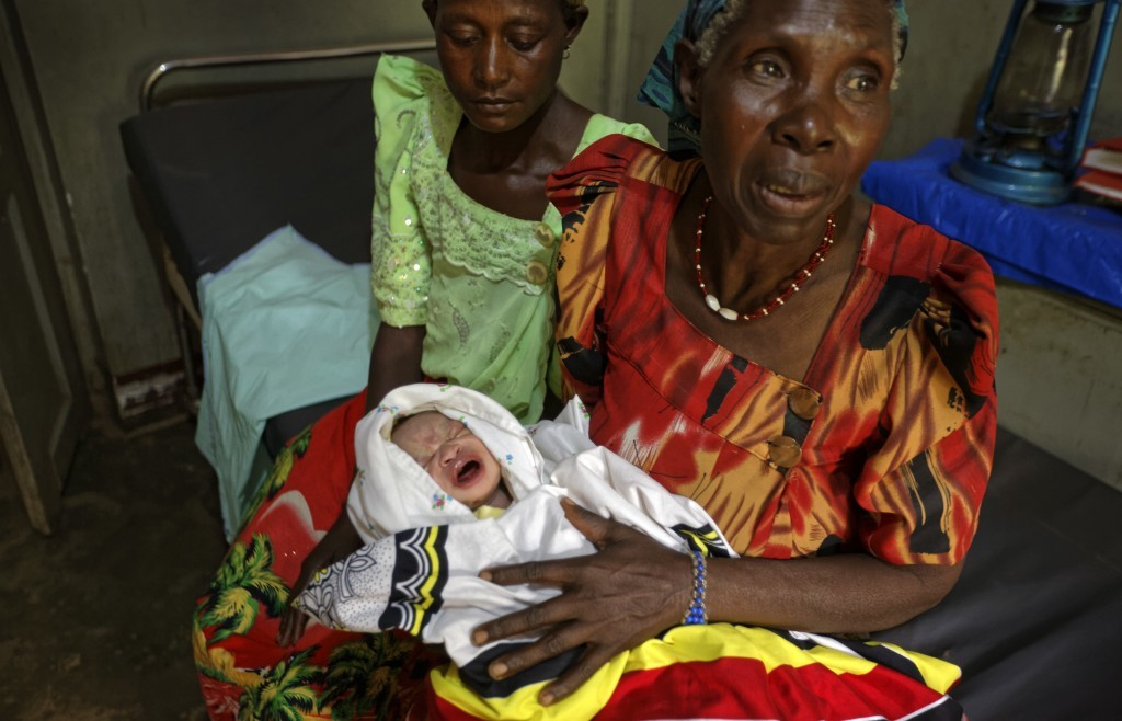 In this Wednesday, May 31, 2017 photo, grandmother Mauda Byarugaba, right, holds her grandson Ben Ssekalunga, who was passed to her by a midwife momen...