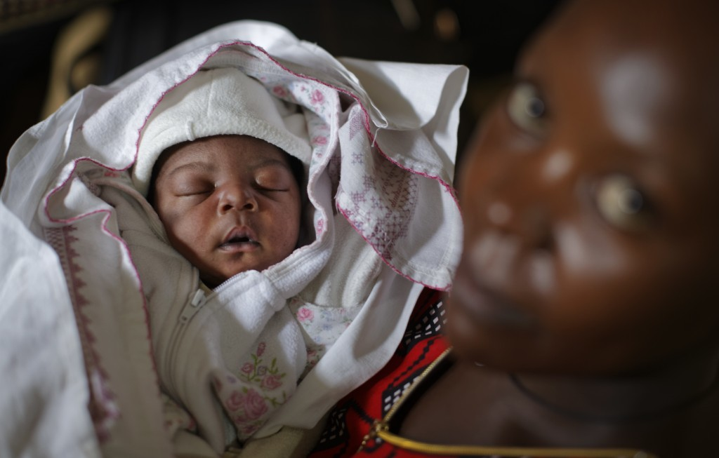 In this Tuesday, May 30, 2017 photo, Mary Nabiryo holds her 1-day-old son, Andrew, in the maternity ward of St. Joseph's Hospital in Kitovu, Uganda. T...