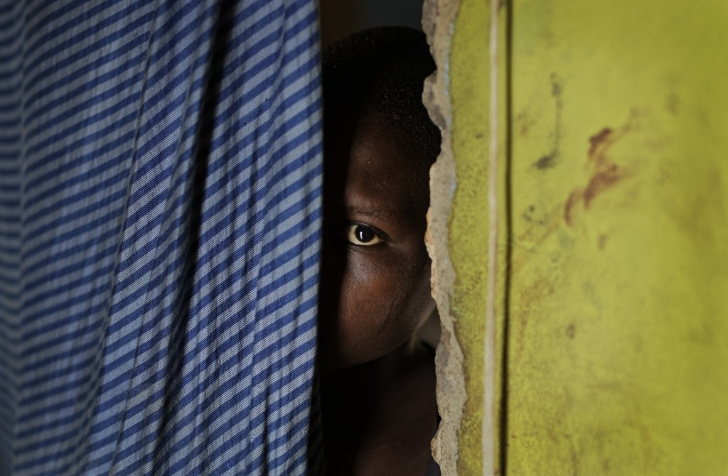 In this Thursday, June 1, 2017 photo, a 15-year-old who was raped when she was 14 talks to a member of UNICEF staff at her home in a village near Masa...