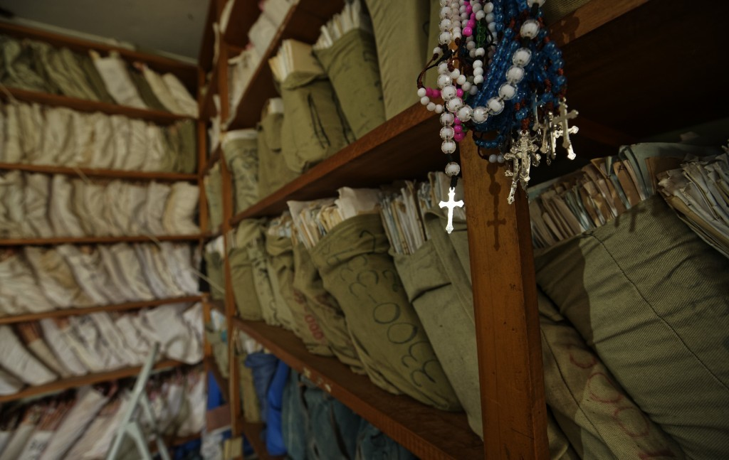 In this Tuesday, May 30, 2017 photo, crucifixes for sale to patients and visitors hang in front of shelves of paper hospital records, including birth ...