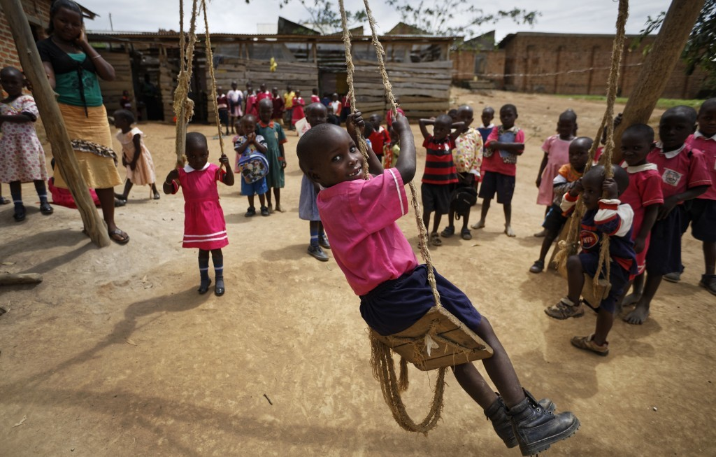 In this Thursday, June 1, 2017 photo, Abdu Kabanda, 6, center, who is HIV-positive and able to receive treatment from a support group because he is ab...