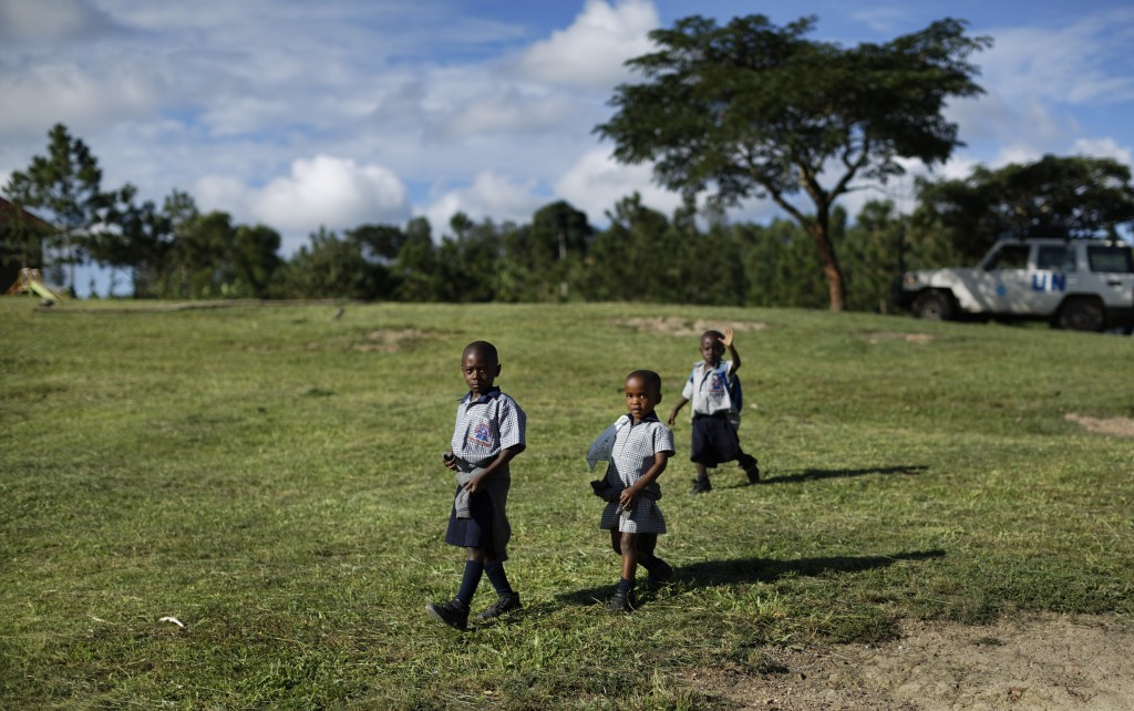 In this Wednesday, May 31, 2017 photo, children walk on the grass during break at the Side-By-Side Boetheo School, which assists mostly orphans who we...