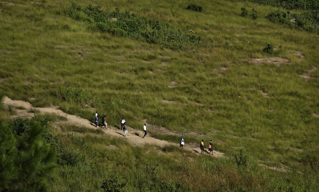 In this Wednesday, May 31, 2017 photo, children from a neighboring school walk past on a hillside near the Side-By-Side Boetheo School, which assists ...