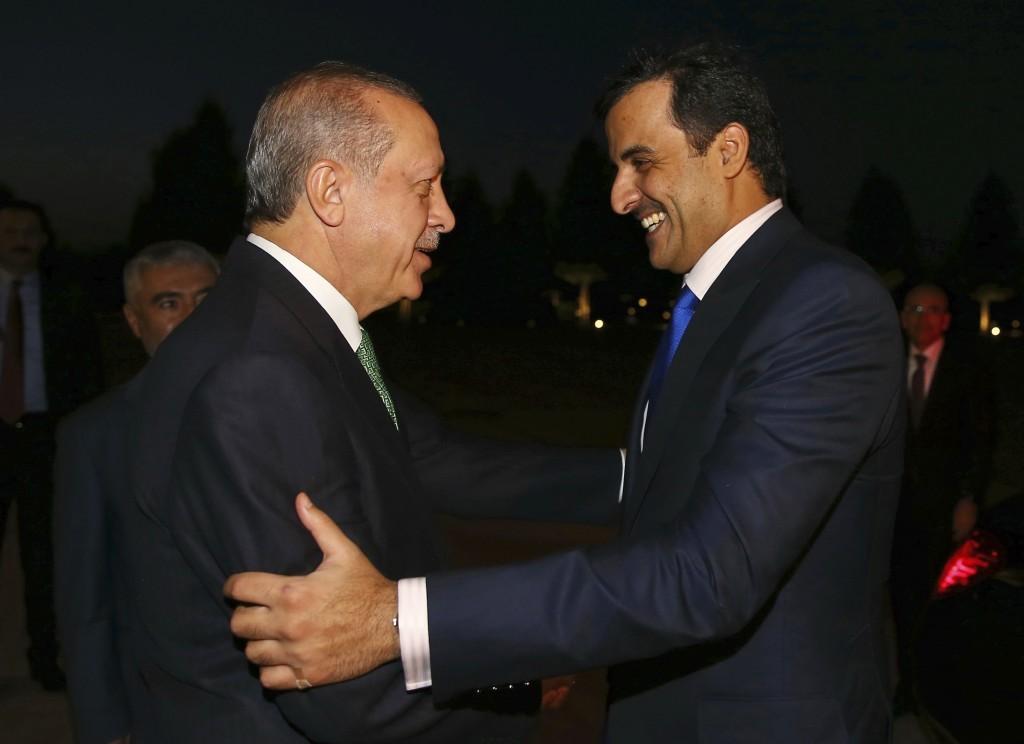 Turkey's President Recep Tayyip Erdogan, left, shakes hands with Qatar's Emir Sheikh Tamim bin Hamad Al Thani prior to their meeting at the Presidenti...