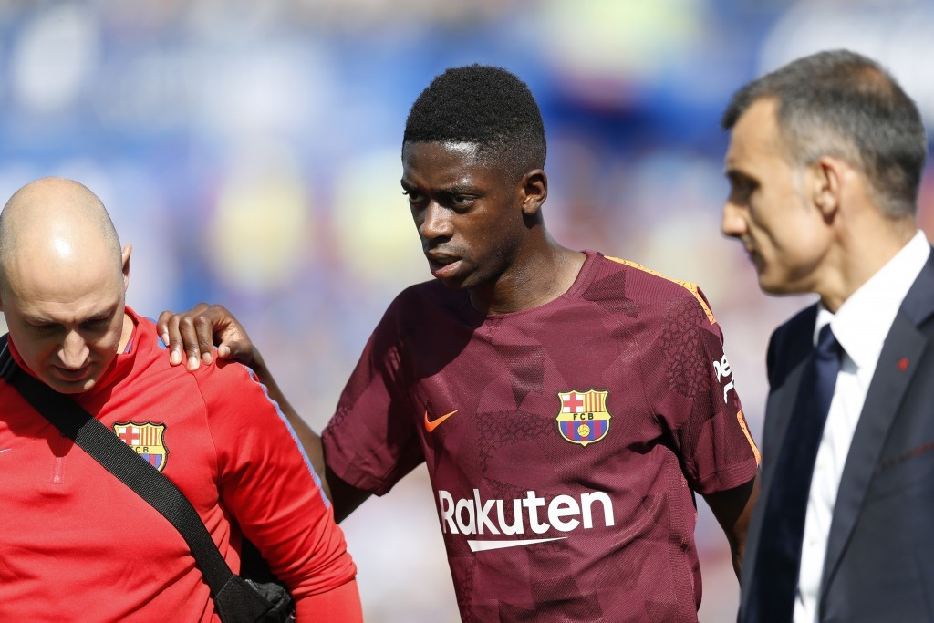 Barcelona's Ousmane Dembele, centre, leaves the pitch injured during a Spanish La Liga soccer match between Getafe and Barcelona at the Alfonso Perez ...