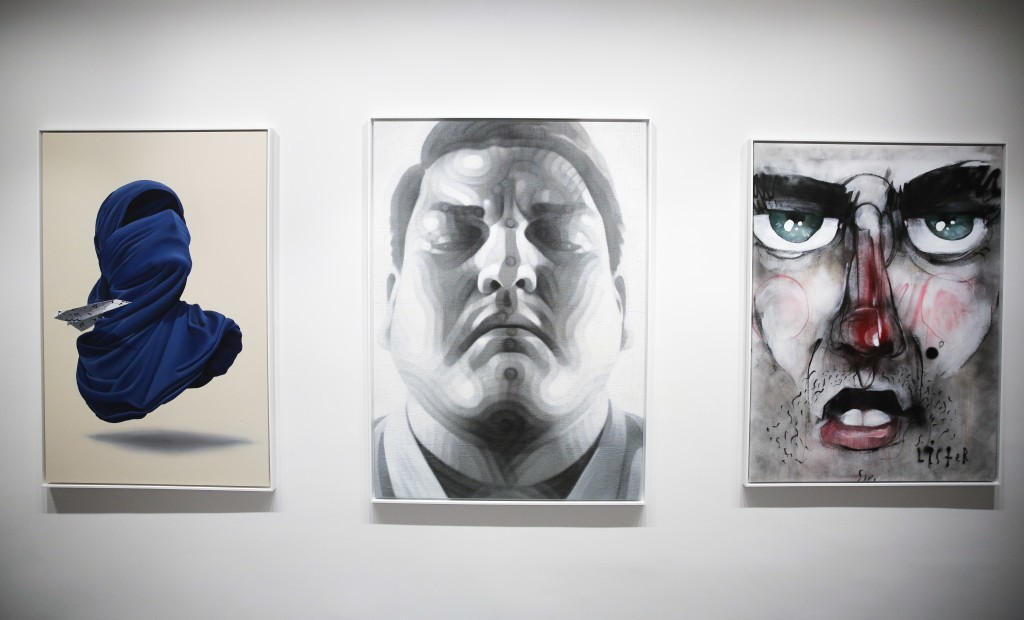 The paintings, from left: 'Shirt Mask x Paper Plane' by Numo Viegas, 'The Fighter' by El Mac and 'Street Face' by Lister displayed inside the exhibiti