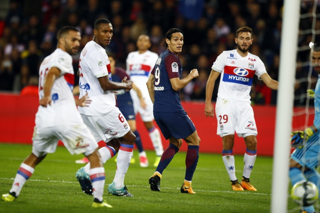 Paris Saint Germain's Edison Cavani, center, eyes the ball after scoring the first goal against Lyon during their French League One soccer match betwe...