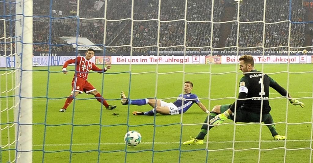 Bayern's James Rodriguez, left, scores his side's second goal against Schalke goalkeeper Ralf Faehrmann during the German Bundesliga soccer match betw...