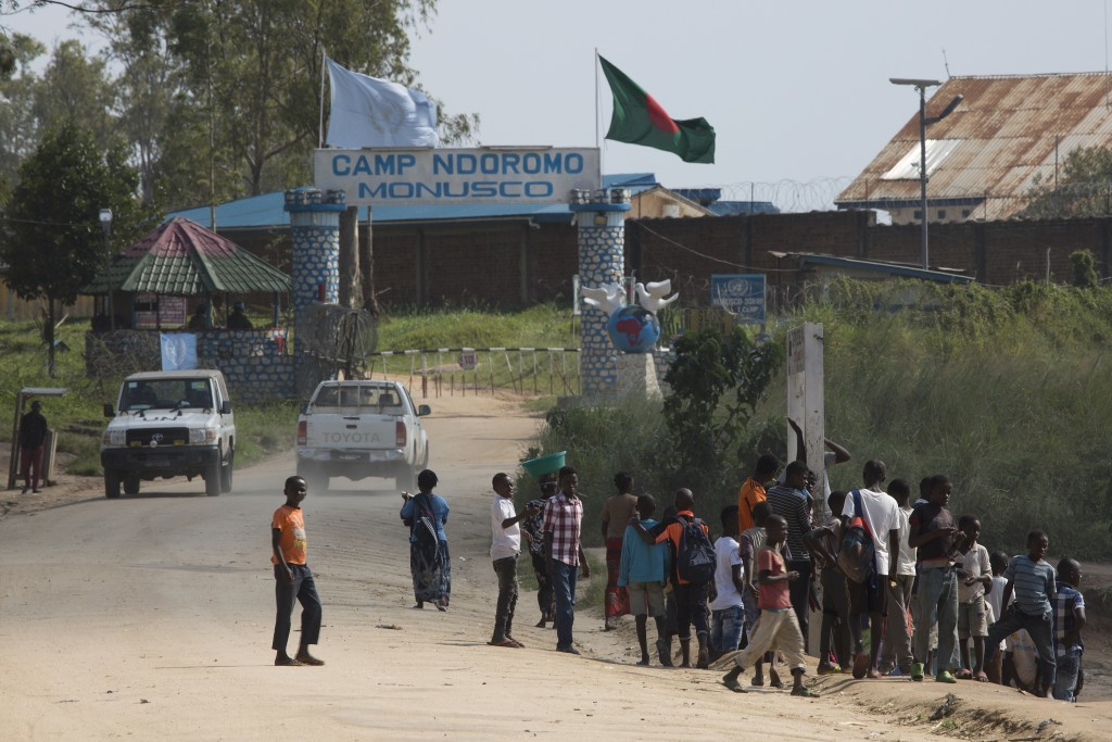In this photo taken Aug. 10, 2016, people gather outside the UN compound in the Congo Ituri province capital Bunia. By virtue of being the largest U.N...