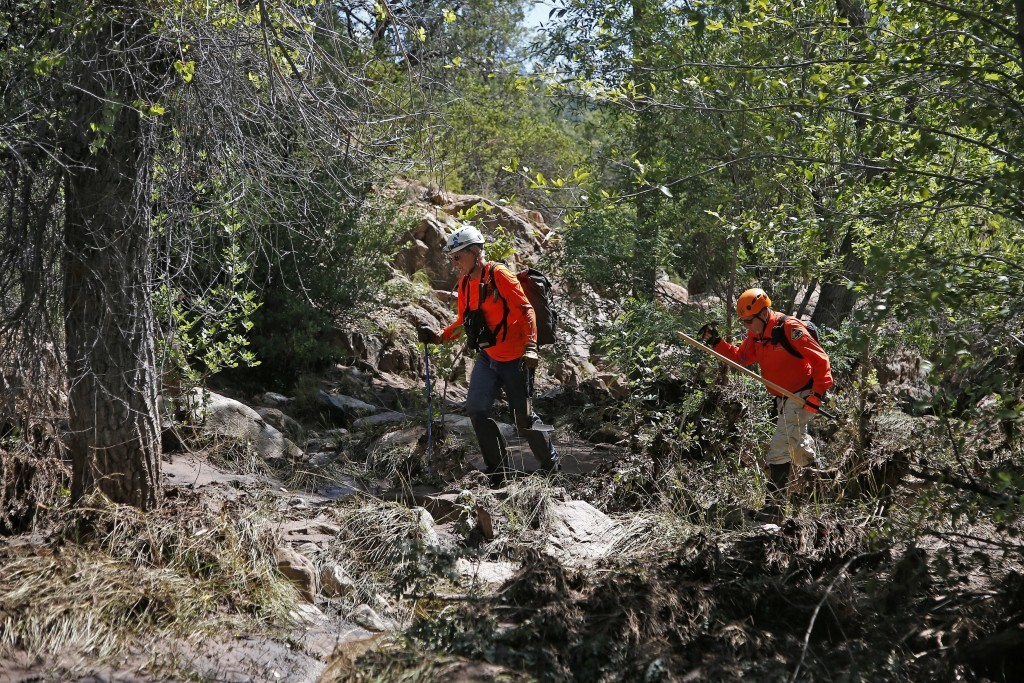 FILE - In this July 17, 2017 file photo, members of the Tonto Rim Search and Rescue Team comb the muddy East Verde River near the entrance to the Firs...