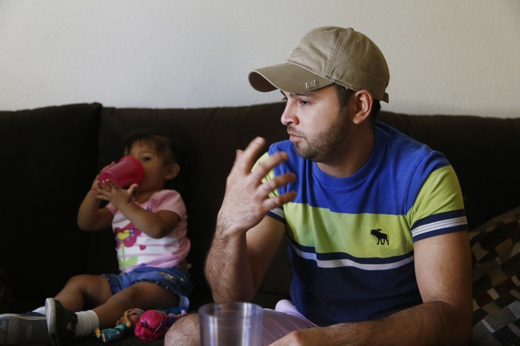 Cesar Garcia, right, talks about how he and other family members, including 1-year-old Marina, left, survived the Payson, Ariz., flash flooding this s...