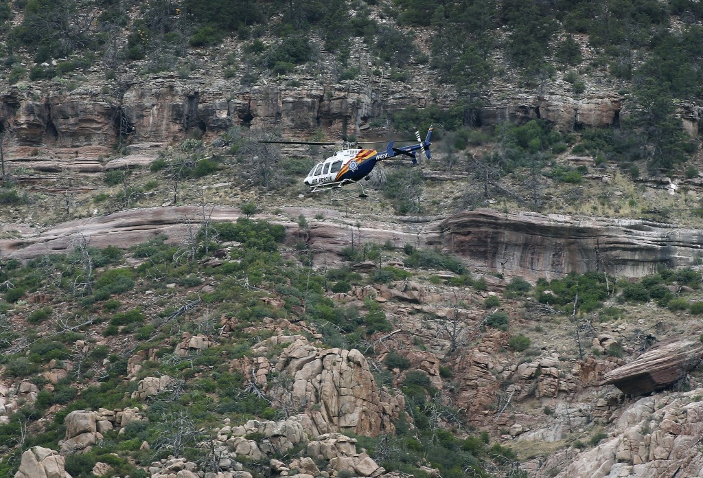 FILE - In this July 16, 2017 file photo, a helicopter flies above the rugged terrain along the banks of the East Verde River during a search and rescu...