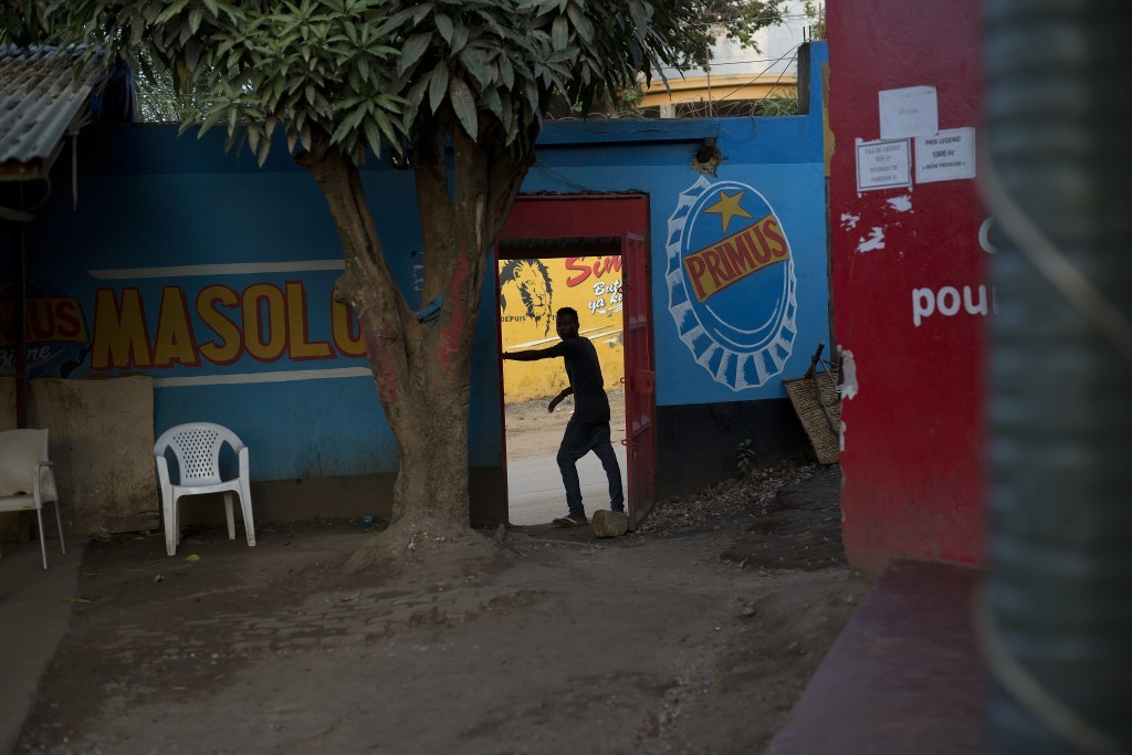 In this photo taken Aug. 10, 2016, a man stands at the entrance of a bar in the Congo Ituri province capital Bunia. Bars and night-clubs are off limit...