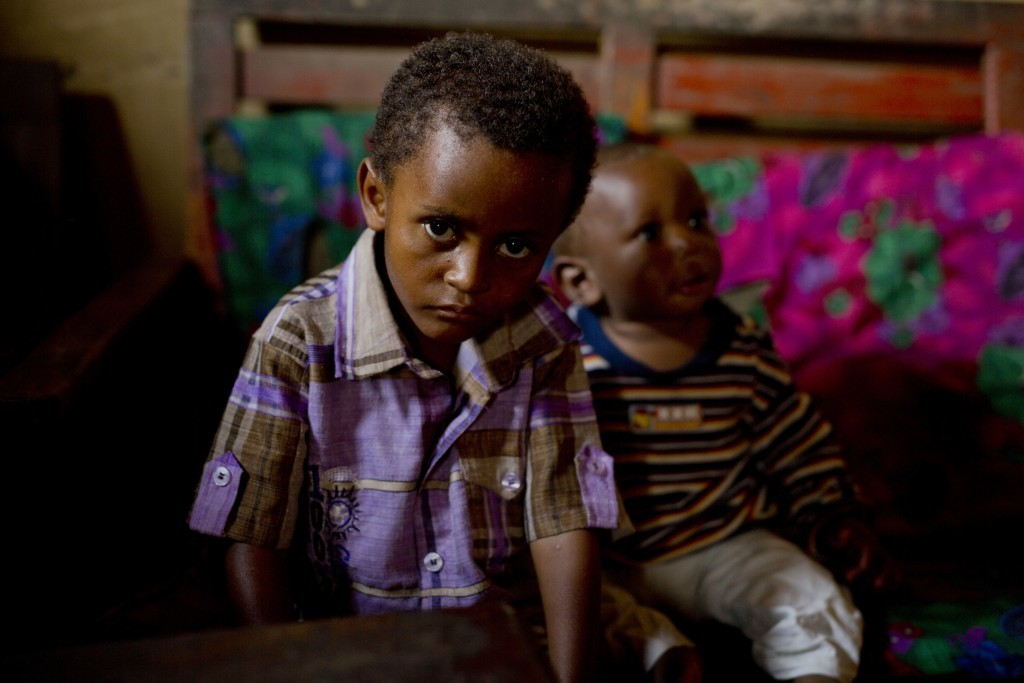 In this photo taken Aug. 10, 2016, 8-year-old Michael sits at his mother's house in the Congo Ituri province capital Bunia. Michael has never met his ...
