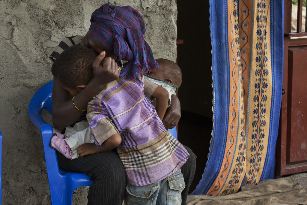 In this photo taken Aug. 11, 2016, 8-year-old Michael is hugged by his mother Blandine at their home in the Congo Ituri province capital Bunia. Michae...